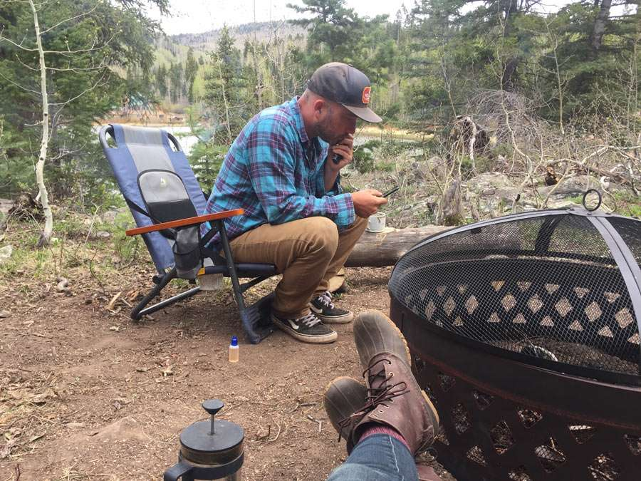 a man looking at a phone near a fire pit