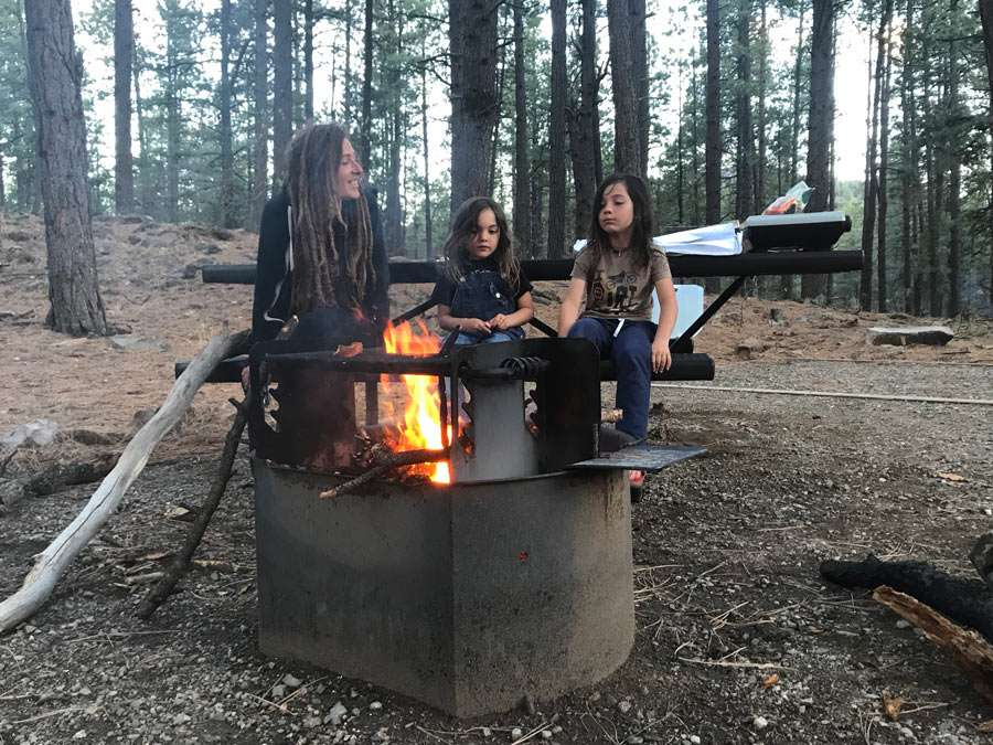 a family camping at a national forest, sitting around a fire on a picnic table