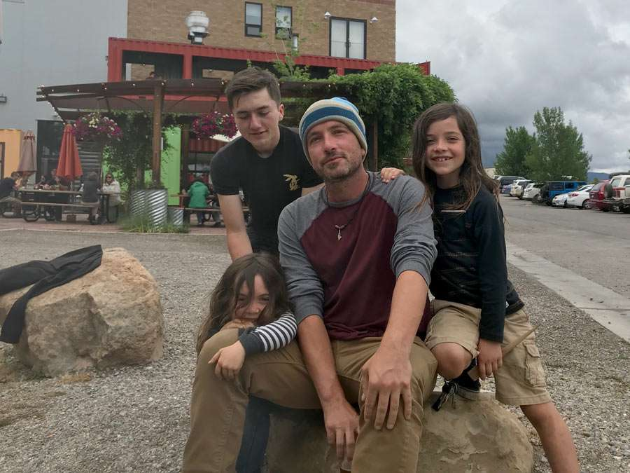 a father sits with his kids in front of Ska Brewing in Durango Colorado