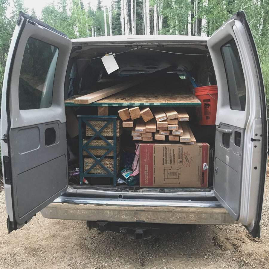 the back doors of a van open, loaded with wood