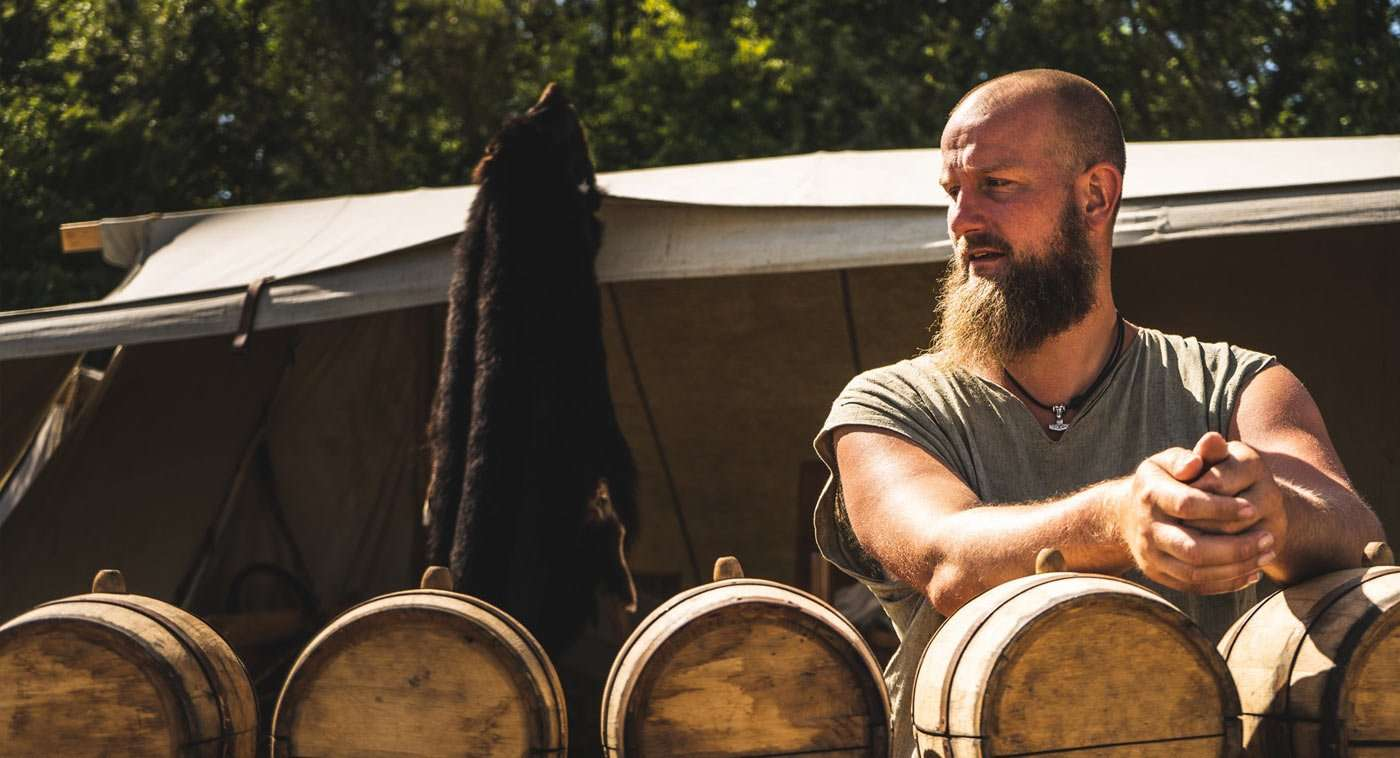 a man and his van in front of some wine barrels