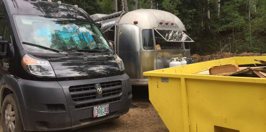 a van, airstream and dumpster in a tight space
