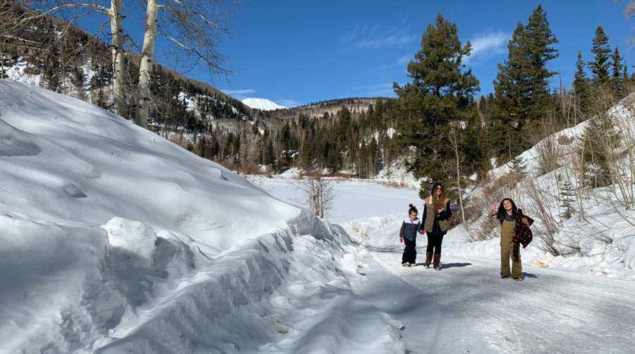 a family walks up a snowy hill on a sunny day
