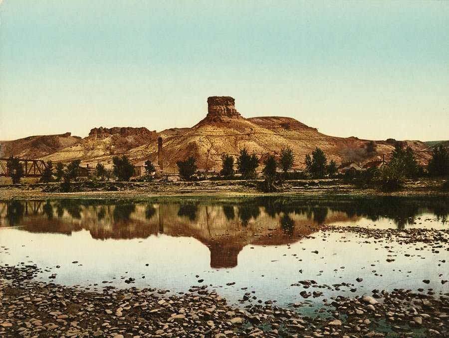 a single rock outcrop stands taller than the mountains around it, Green River flowing in the foreground