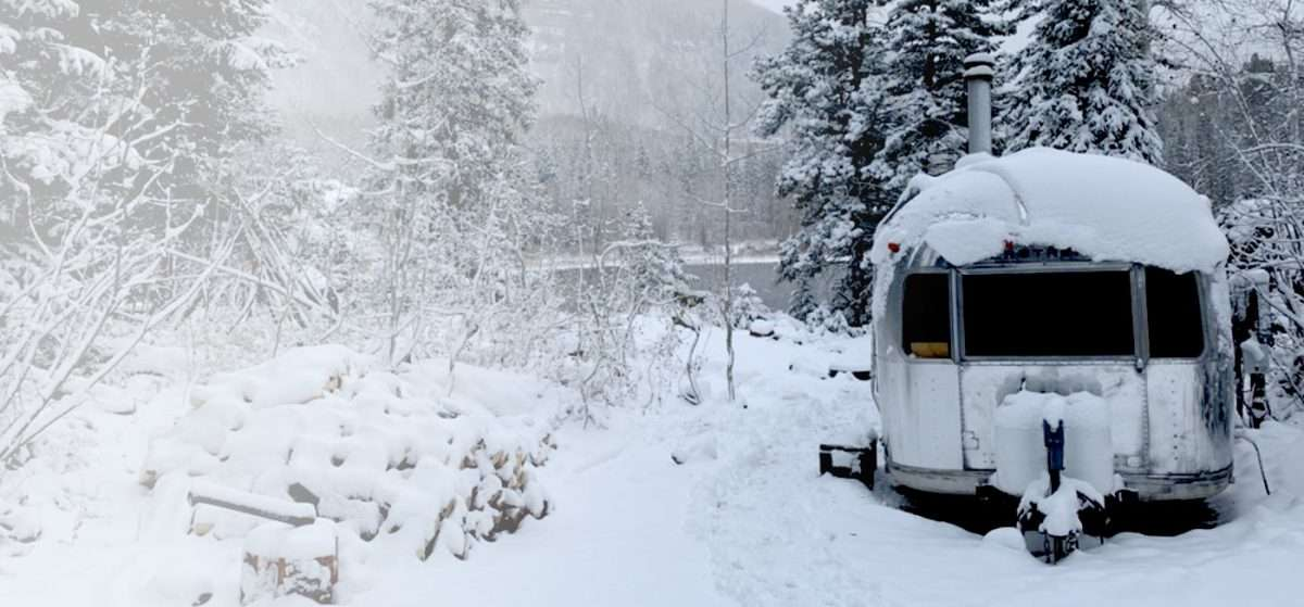 an Airstream parked in the snow by a lake in the mountains