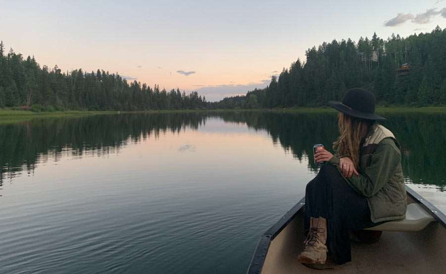 a woman with a beer in her hand sitting in a canoe on a lake at sunset