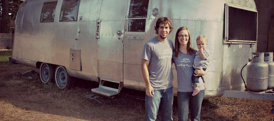 a young couple and their newborn stand in front of a vintage Airstream