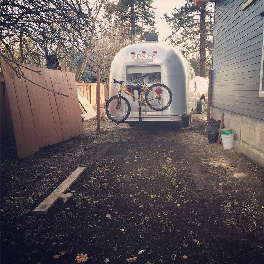 an Airstream pulling out of a space next to a friends home