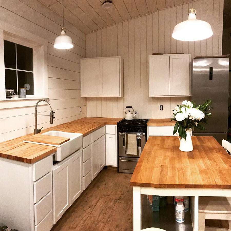 a beautiful wooden and white kitchen in a tiny home