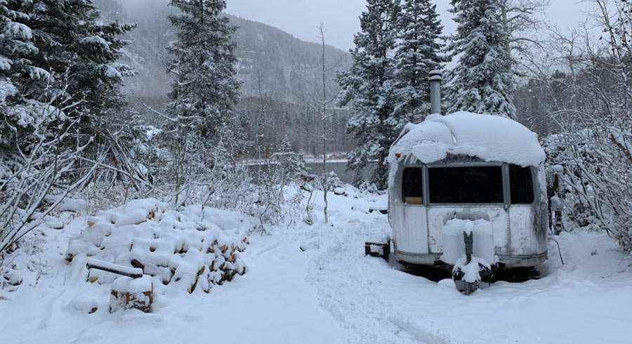 an Airstream surrounded by snow