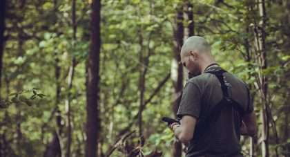a man in the forest checks his physical mail via his phone