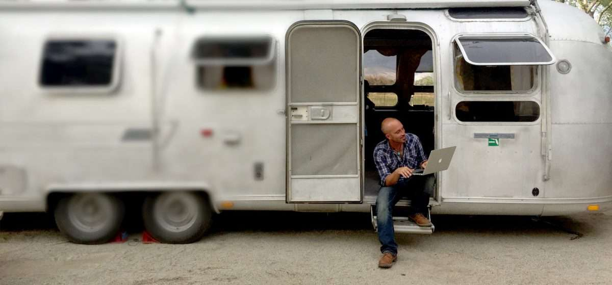 a man on a laptop sitting in an airstream doorway