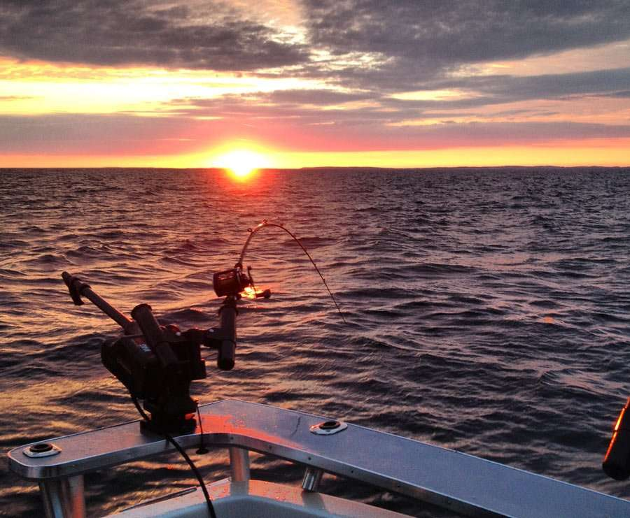 sunrise over a fishing charter on lake michigan