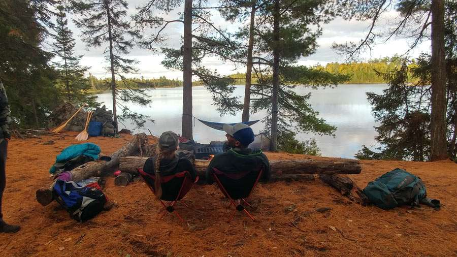 the couple relaxing at their campsite near a lake