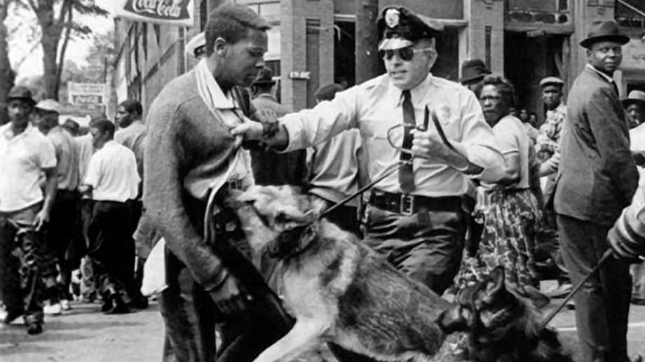 a police officer with a vicious dog, both grabbing at a black man who does not appear to be resisting their attack