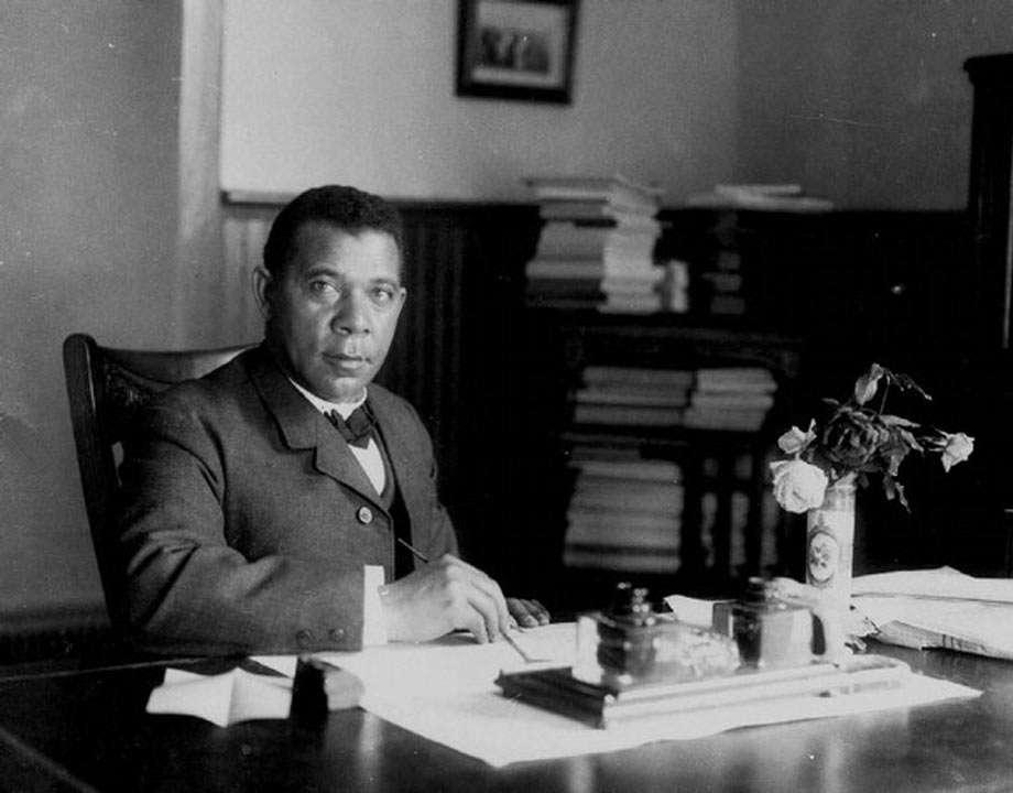 Booker T. Washington sits at his desk
