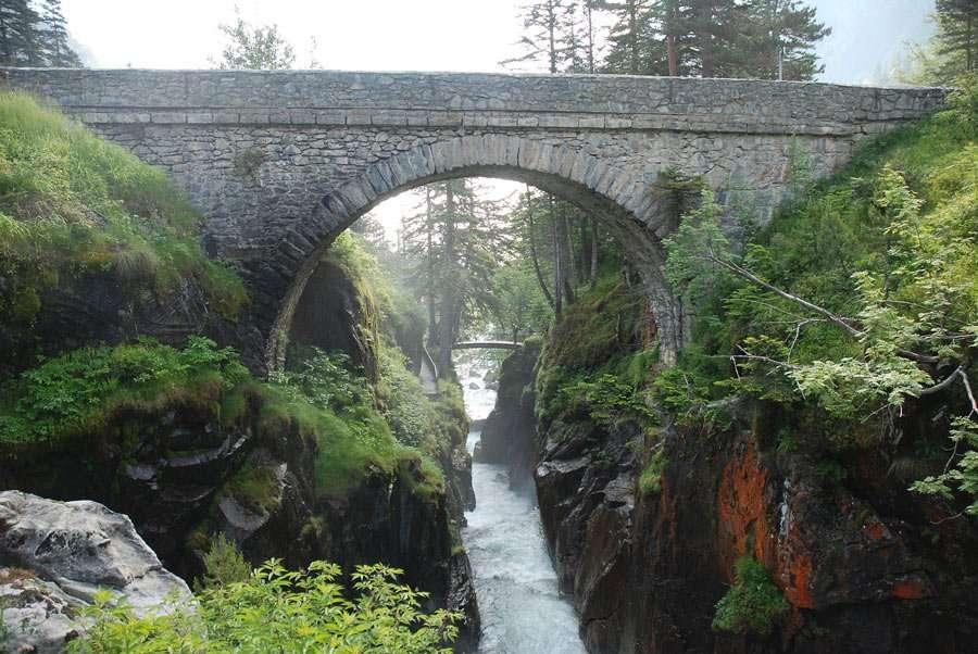 a stone bridge crosses a river