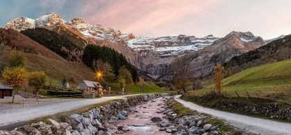 a river runs along a roadside, with a small building and streetlights lining that, through the French Pyrenees
