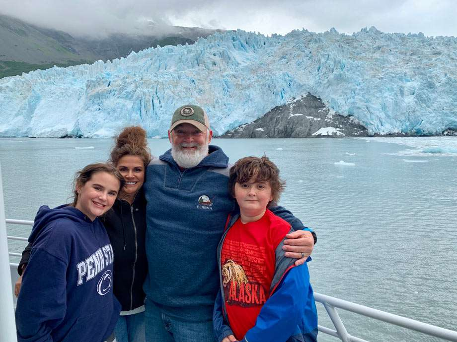 a family of four stands before a massive glacier