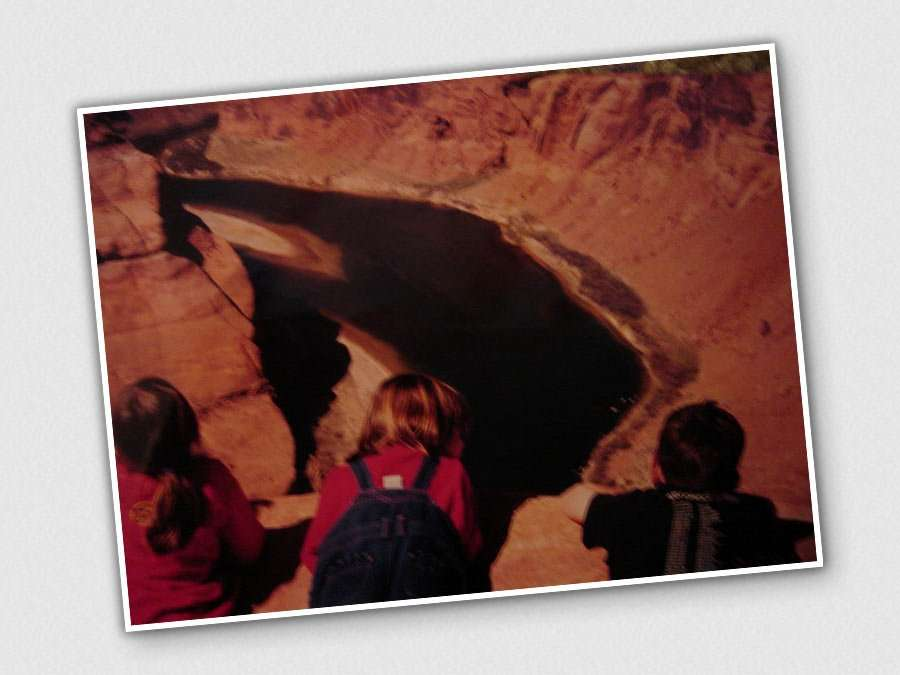 three young children in a photo taken before the Internet knew what to do with itself stare at a canyon