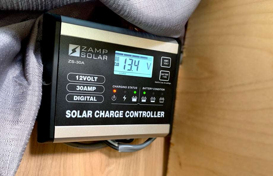 a ZAMP solar charge controller, a small rectangular box, not much bigger than a hand, displays various charging statuses of the battery and solar panels