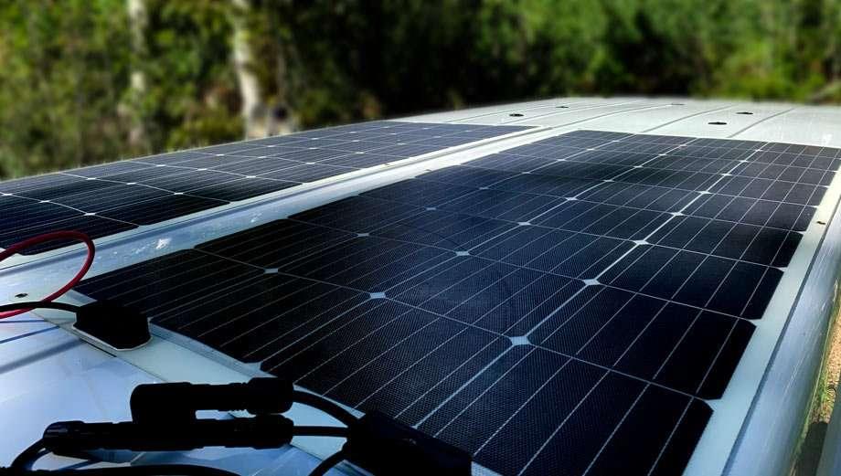two 160 watt solar panels, crisp and black against the top of a van roof