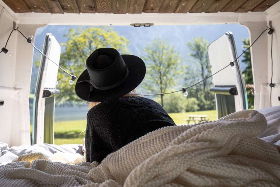 a young woman in a black stetson hat, lying in bed, looking out the back window