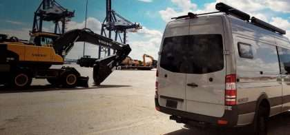 a sprinter van sits on a shipping dock, waiting to be hustled off to Europe