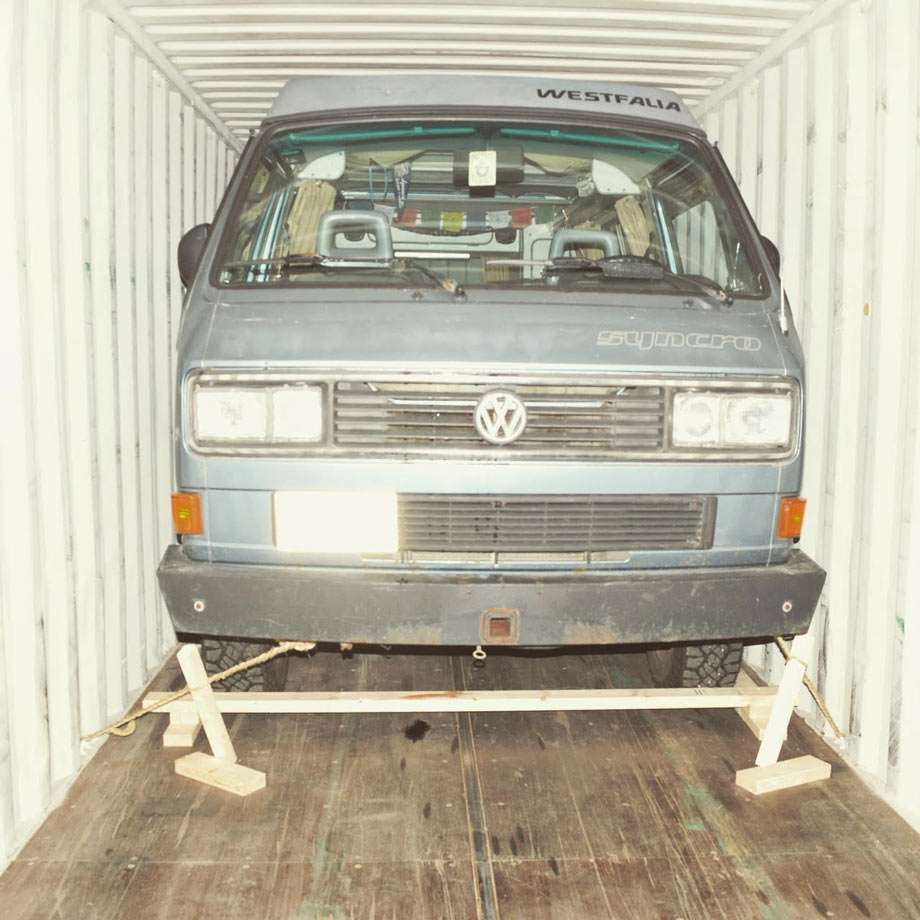 a light blue vanagon in a shipping container, bound for Europe