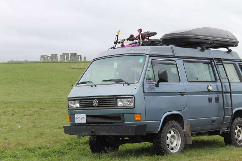a vanagon parked in a field, the stacked rocks of stonehenge in the background
