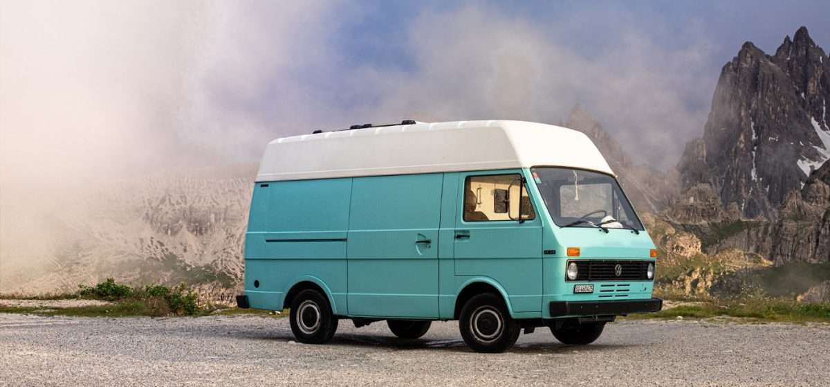 a baby blue VW LT parked in a lot near massive mountains