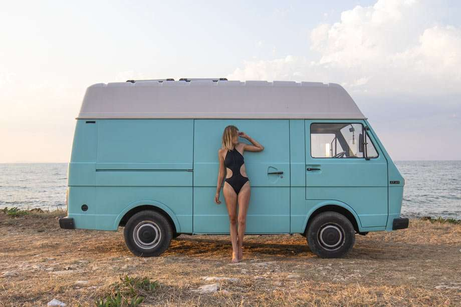a woman in a bathing suit and stetson hat stands in front of her van, on a beach