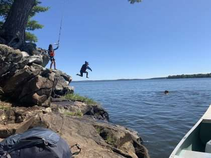 A boy jumps from a rock ledge into the waters of Lake Kabetogama