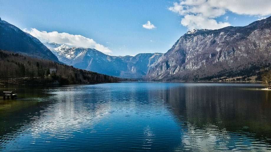 a large lake, nestled between mountain cliffs peppered with snow