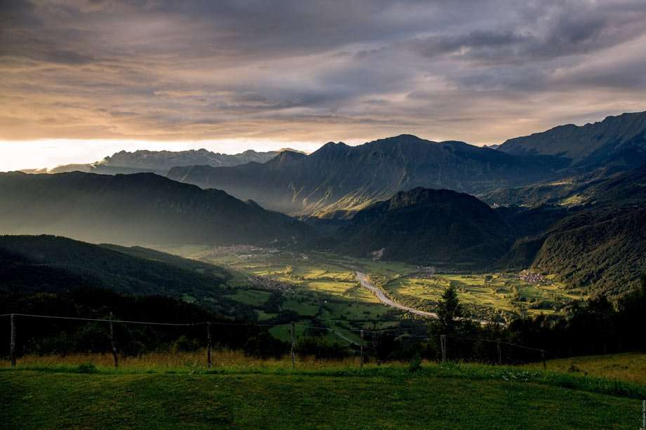 violet and golden sun rays set over truly majestic hills of contrasting shadowy darkness and rolling green pasture