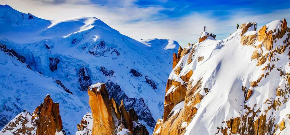 snow-covered Alps, hikers looking down from a ridge
