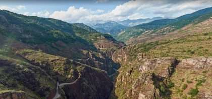 a majestic canyon, river and road stretching through nature's grandeur