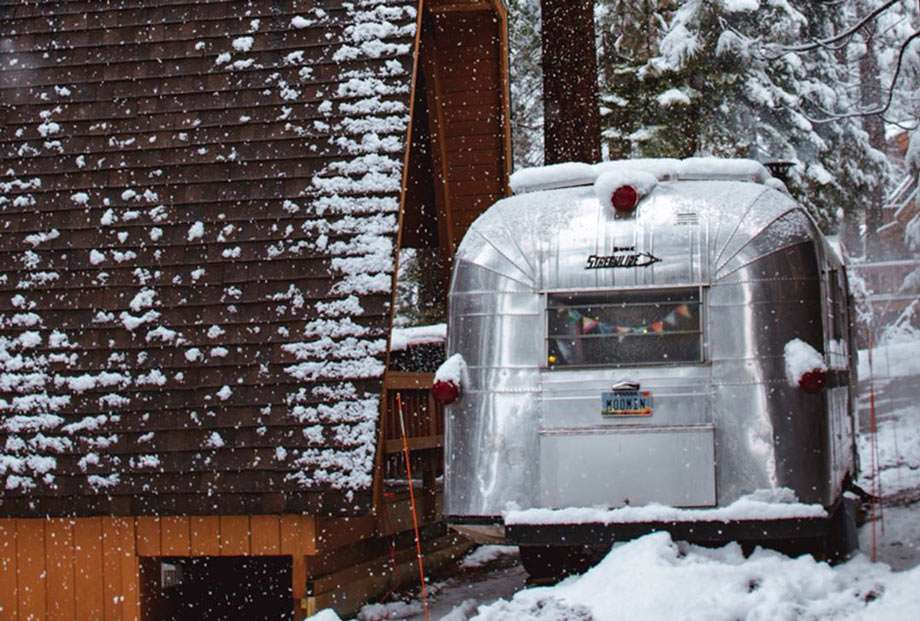 a vintage silver travel trailer parked beneath an a-frame cabin, both coated in snow