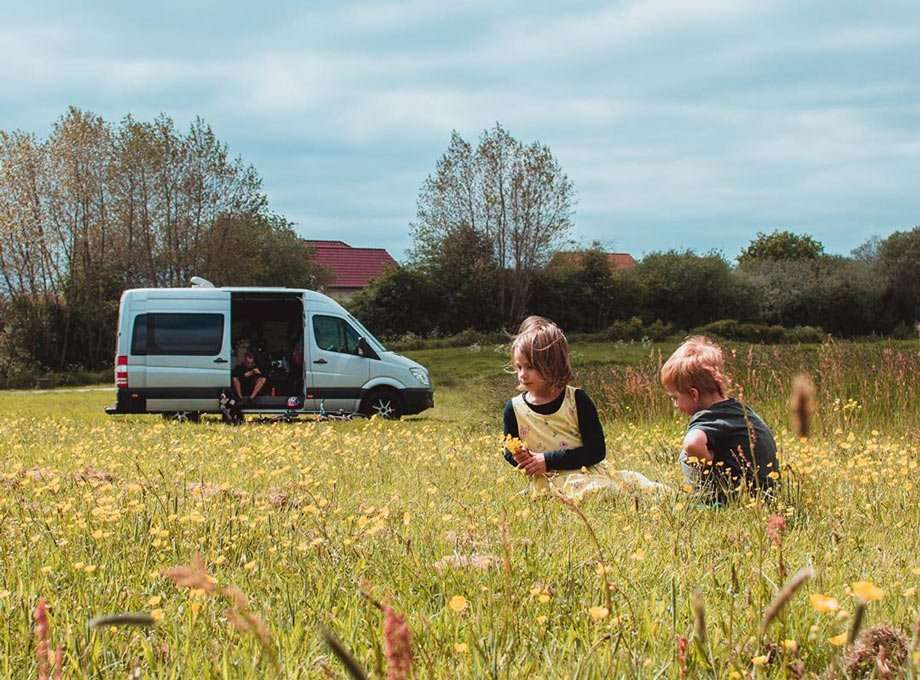 two children play in a field, a van, their home, in the background
