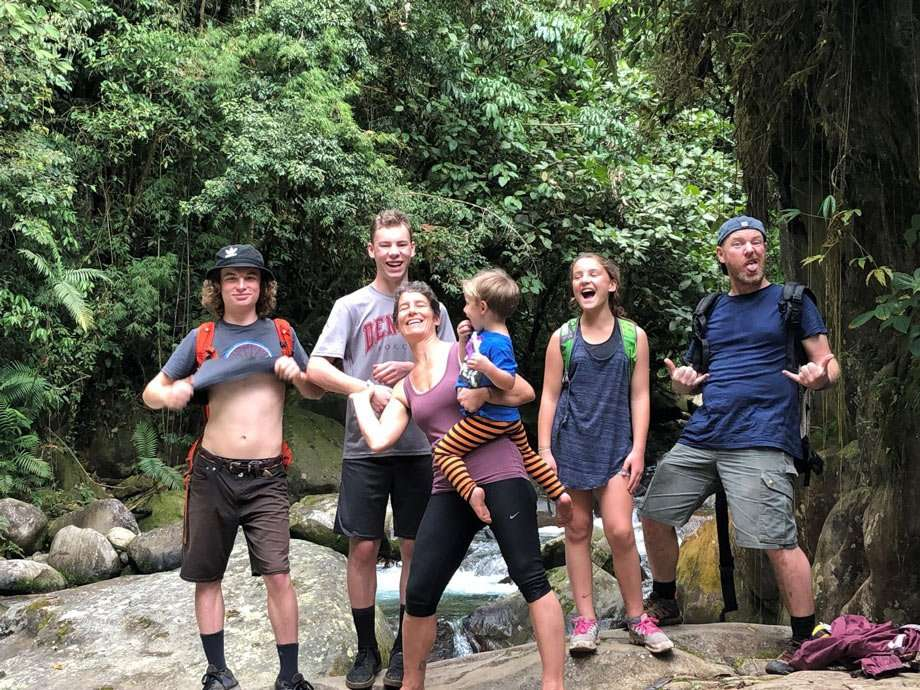 a family of six, including teenagers, mom and dad and a young one, posing with funny faces in Costa Rica