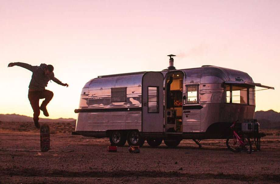 a man doing a skateboard trip, his shiny travel trailer in the background, in the desert