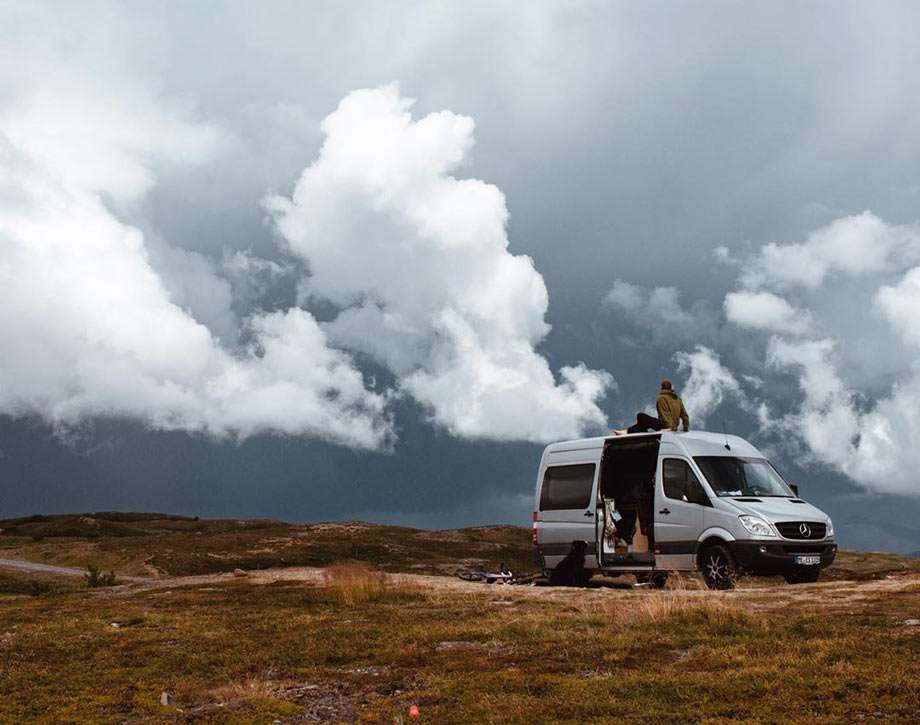 a man sitting atop his van in europe, drastic skies fill the background
