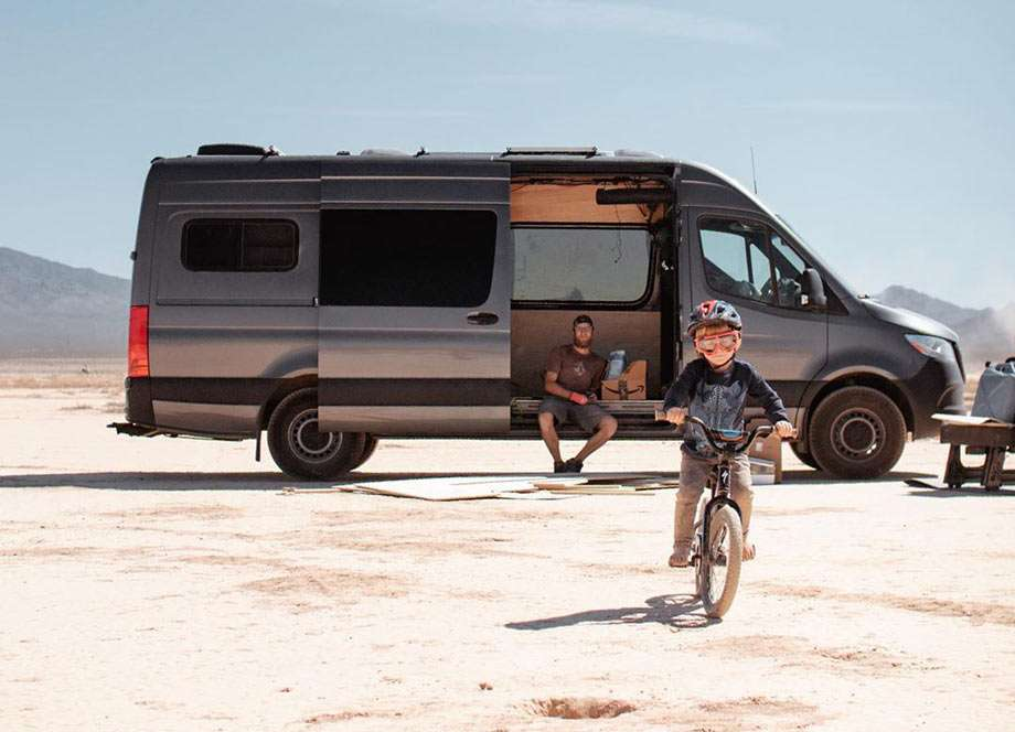 a young boy rides his bike away from a sprinter van in which dad's sitting in the door