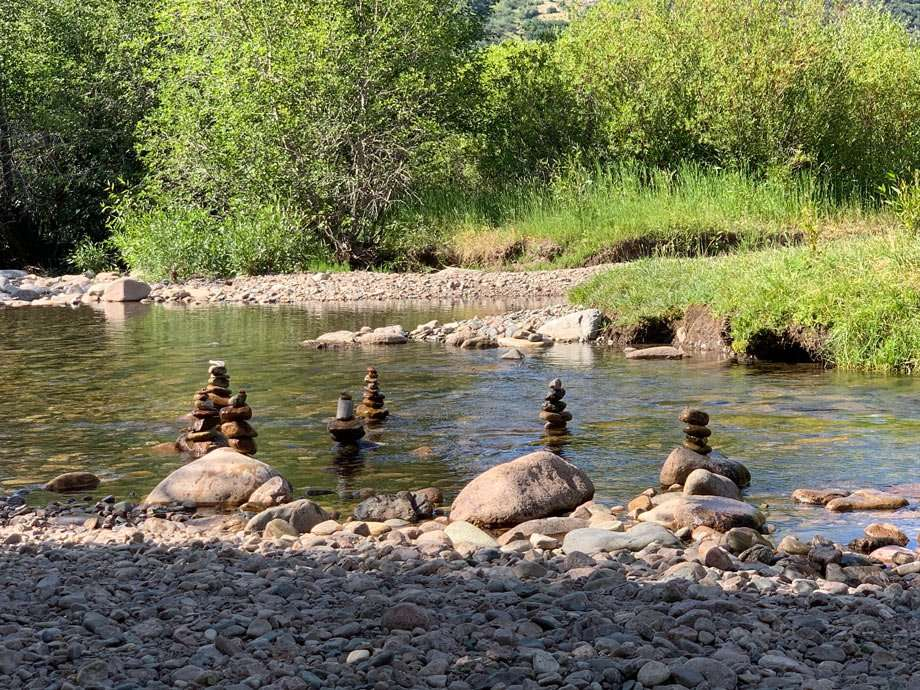 cairns stacked in a shallow creek