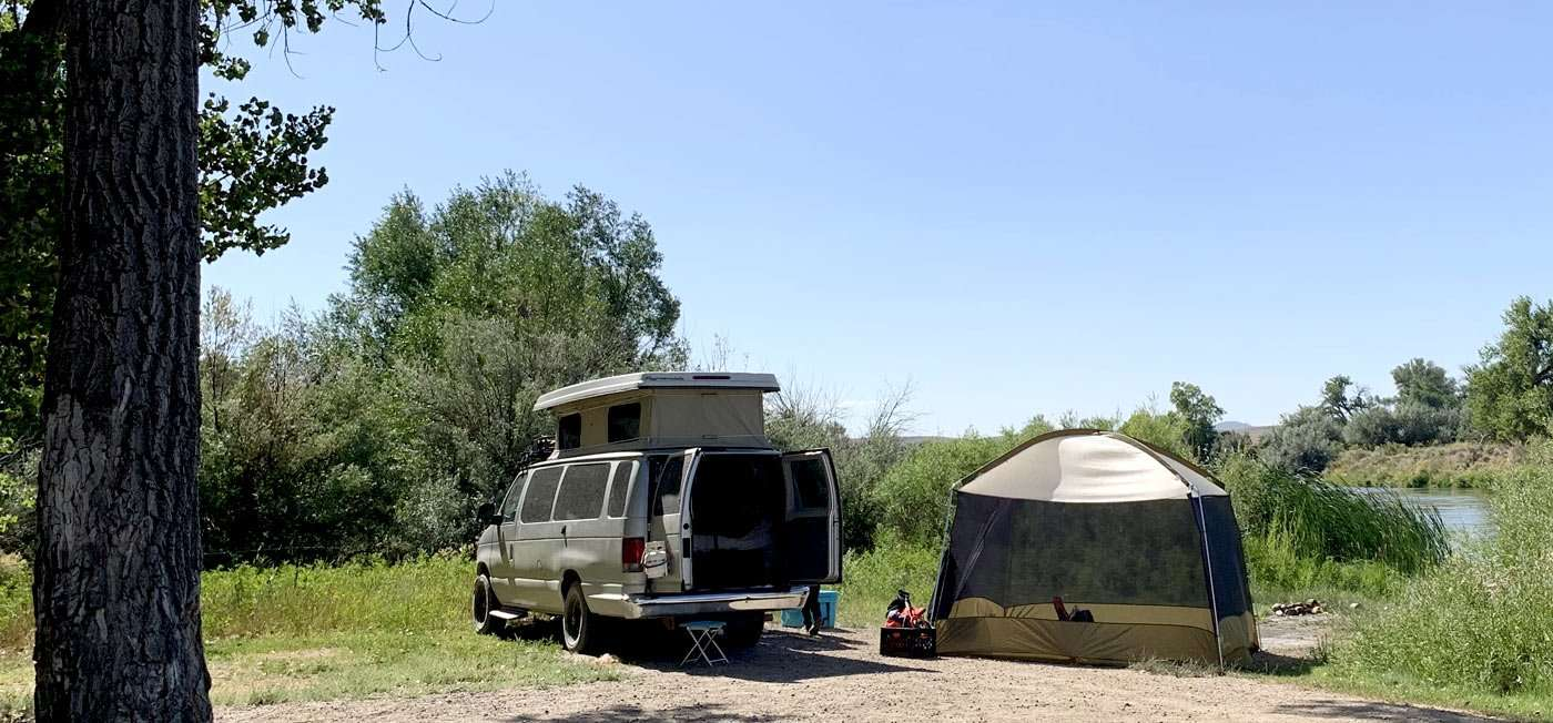 a van and tent camping near a river in Wyoming