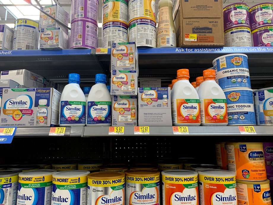 a multitude of colors and varieties of baby formula on shelves in a grocery store