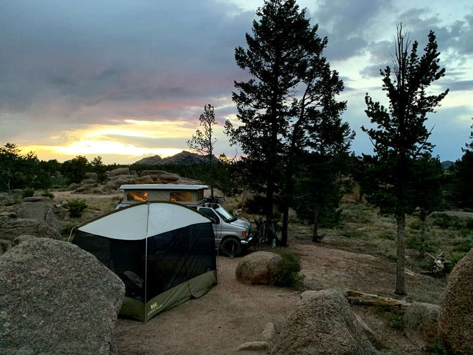 a campsite with tent, van, cooler and views