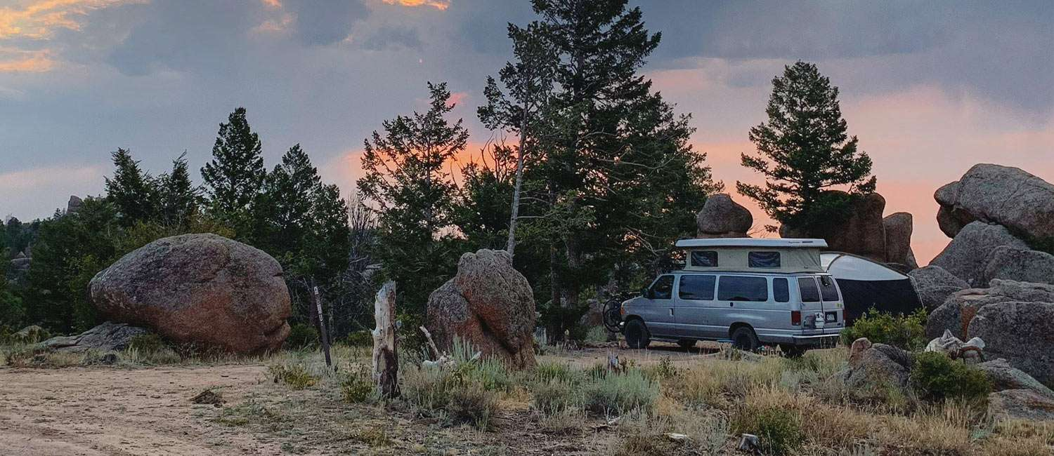 a van camping beneath a dramatic sky in Wyoming's Medicine Bow National Forest