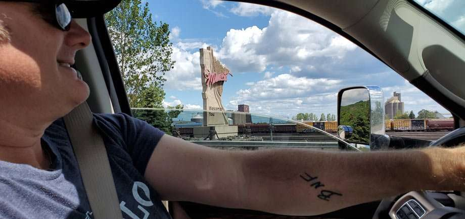 "a man behind the wheel of a truck, a sign reads ""Minnesota welcomes you"" through the window"