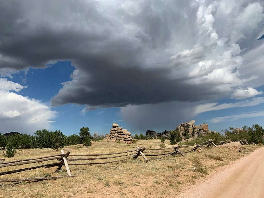 a moody sky sees rain falling from distant storm clouds over the Wyoming desert